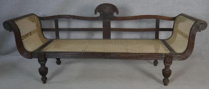 A 19th century Eastern teak double scroll end sofa with carved and reeded frame and caned back and