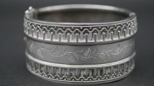 A Victorian engraved white metal cuff bangle with wirework detailing and foliate garland design.