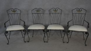 A set of four wrought metal conservatory dining chairs with cut floral upholstered seats on