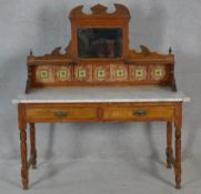A late Victorian satin walnut washstand with carved and tiled mirrored upstand above marble top