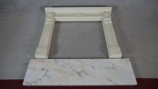A faux polished marble fire surround in the Classical style with floral decorated frieze and
