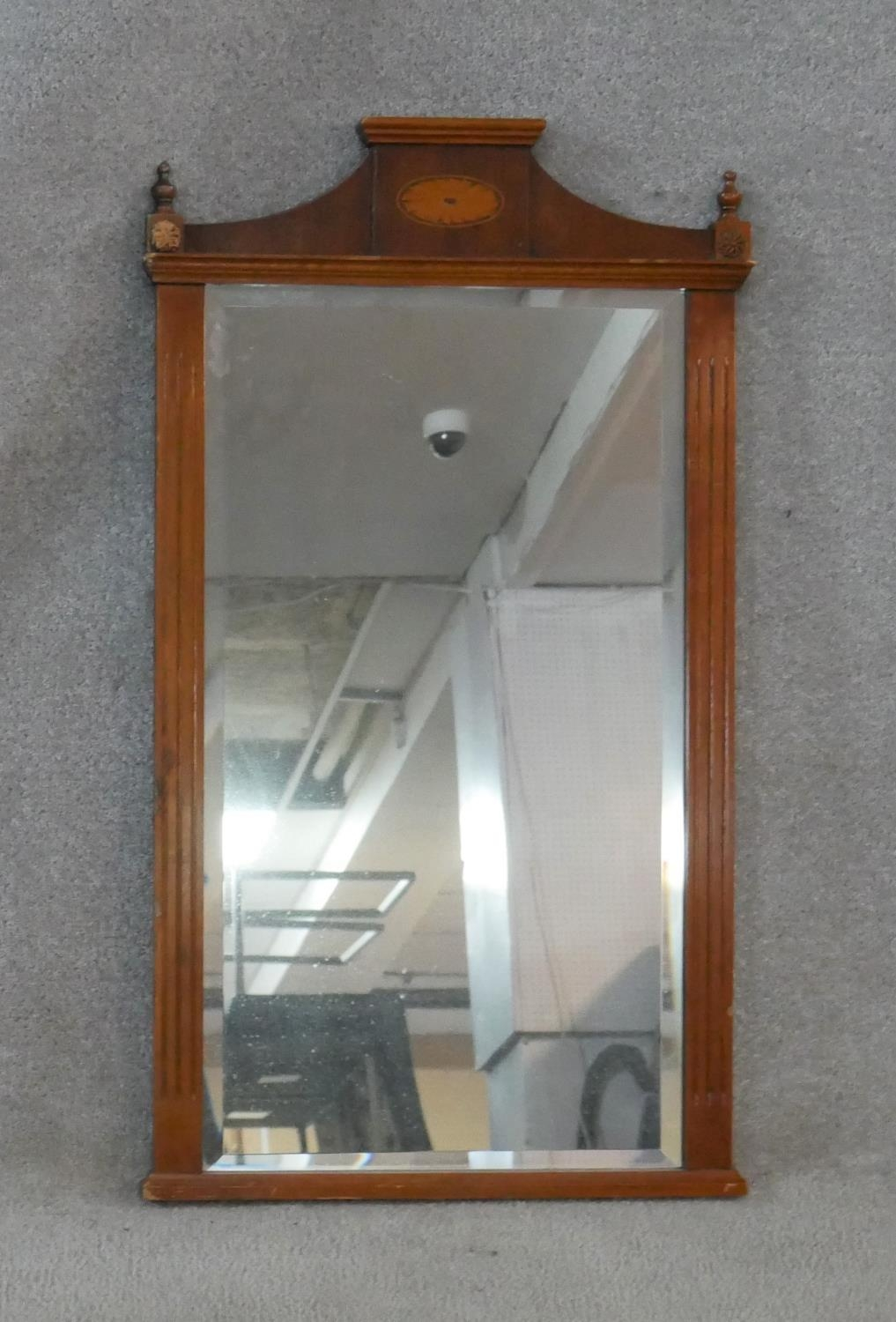 An Adam style yew framed wall mirror with inlaid patera and urn finials to the cresting and bevelled