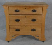 A late 19th century satin walnut chest of drawers with original Art Nouveau handles, carved frieze