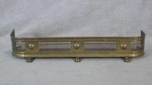 A 19th century pierced brass fire fender on lion's paw feet. H.19.5 W.107 D.14cm