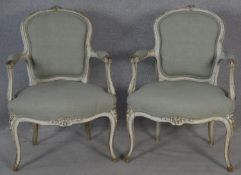 A pair of distressed painted Louis XV style armchairs with floral carved cresting in pale calico