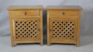A pair of Eastern hardwood bedside cabinets with frieze drawers above lattice panelled cupboard