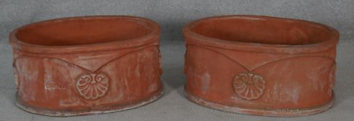 A pair of terracotta garden planters with raised Classical style palmette decoration. H.26.5 L.56