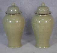 A pair of Chinese crackle glazed lidded temple jars with character marks to the bases. H.65cm