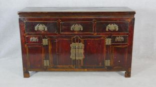 An antique Chinese lacquered sideboard with drawers and cupboards and brass hinges and locks