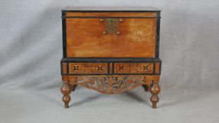 A Nineteenth Century Ceylonese hardwood and ebonised coffer on carved stand fitted with two base