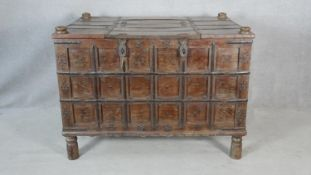 An Eastern metal bound and studded hardwood panelled coffer raised on circular section supports. H.