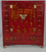 A Chinese red lacquered and hand gilded cabinet with central panel doors flanked by spice drawers