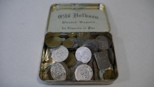 A vintage tin filled with a large collection of antique and vintage shop, gaming and other tokens.