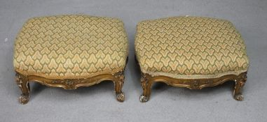 A pair of late 19th century carved giltwood footstools in tapestry upholstery on squat Rococo carved
