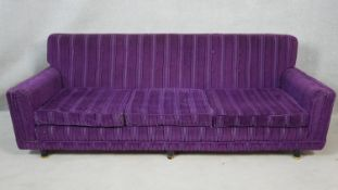 A 1970's vintage cut fabric three seater sofa on ebonised circular supports, retailed by Heal's. H.