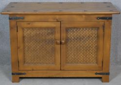 An Eastern teak brass bound side cabinet with rattan panelled doors on block feet. H.62 W.95 D.47.