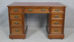 A late 19th century oak pedestal desk with tooled inset leather top and original brasswork on a