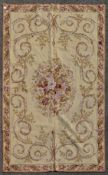 A needlepoint rug with central floral spray and scrolling foliage on a biscuit ground within leaf