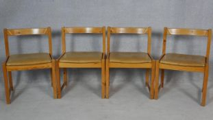 A set of four vintage pitch pine dining chairs with light tan leather upholstered seats. H.75cm