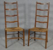 A pair of C.1900 oak ladderback chairs with woven rush seats on circular stretchered supports. H.