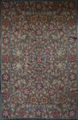 A needlepoint carpet with all over naturalistic flowerhead and leaf design within a wide floral