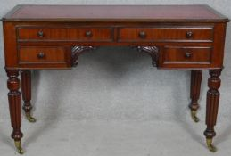 A 19th century mahogany kneehole writing table with inset tooled teather top raised on tapering