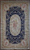A needlepoint rug with central floral oval medallion on a midnight field contained by foliate