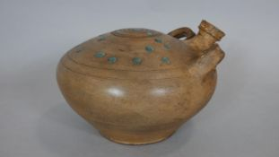 A ceramic glazed Persian water vessel with spout and two handles. Turquoise glaze dots to the
