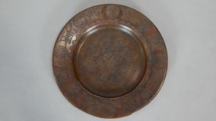 A copper Zand dynasty style plate impressed with various calligraphic motifs and stylised foliate
