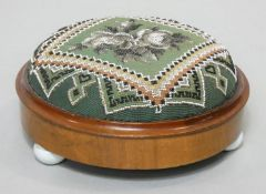 A Victorian mahogany framed footstool in it's original beaded tapestry upholstery on three ceramic