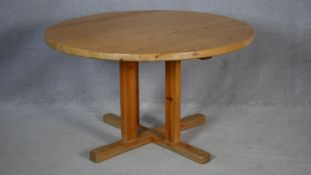 A pine circular kitchen table on quadruped platform supports. H.70 D.120cm