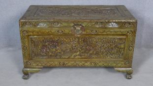 A mid century Chinese camphor wood coffer with hinged lid and all over carving on squat cabriole