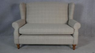 A contemporary Georgian style two seater wing back sofa in window pane upholstery on turned tapering