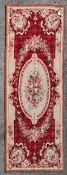A needlepoint rug with central floral cartouche on a burgundy field within ribbon and flowerhead