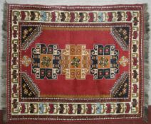 A Turkish Kars rug with repeating medallions on madder ground within spandrels and stylised lotus