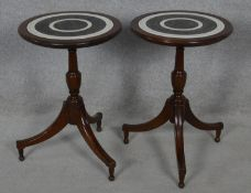A pair of Colonial style occasional tables with carved and stained tops on tripod pedestal bases.