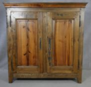 A 19th century style French Provincial elm armoire with panelled doors enclosing adjustable linen
