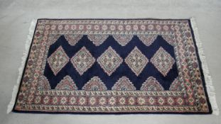 An Eastern rug with repeating lozenge medallions on midnight ground within stylised foliate multi