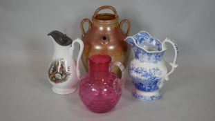 A Victorian cranberry glass jug, a stoneware flagon and two other milk jugs. H.34cm (Tallest)