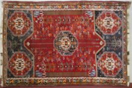 An Eastern carpet with central pole medallion on a madder field within midnight stylised borders.