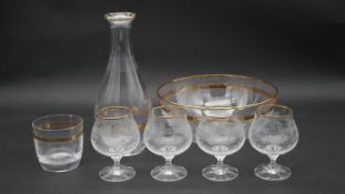 A gilded foliate design glass decanter with matching bowl, tumbler and four gilded and etched cognac