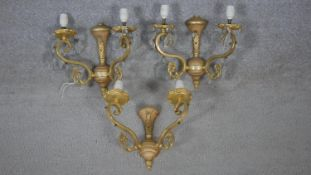 A set of three gilt metal twin branch wall sconces with scrolling arms and crystal drops. W.27cm