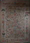 A needlepoint carpet with profuse flower and leaf design across the beige ground contained by floral
