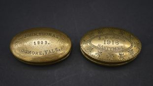 Two antique engraved oval brass Welsh miners snuff boxes. One inscribed John Thomas, 1903, Ogmore