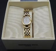 A boxed Raymond Weil gold plated ladies wristwatch with papers. It has an oval face with white