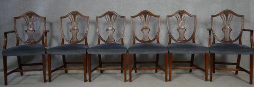 A set of six mahogany Hepplewhite style dining chairs with pierced wheatsheaf backs above stuff over