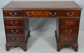 A Georgian style flame mahogany pedestal desk with inset gilt tooled leather top above an