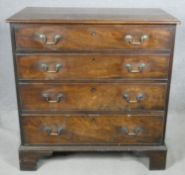 A Georgian mahogany chest of four long graduating drawers with brass swan neck handles on bracket