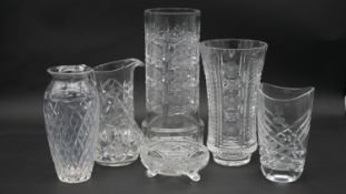 A collection of fine cut crystal items. Including four cut crystal vases, a cut crystal water jug