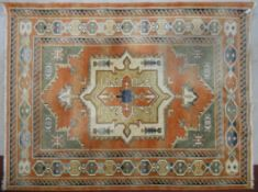 A Turkish Anatolian carpet with central medallion on salmon ground within stylised geometric